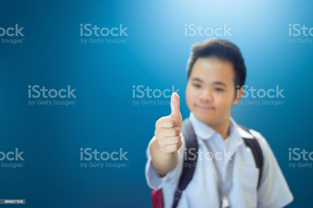 A student in school uniform giving a thumbs up. stock photo