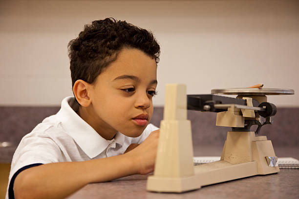 Student in science class using balance. stock photo