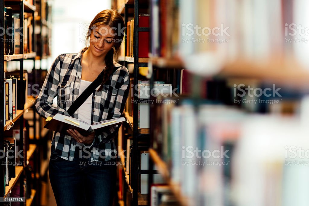 Student in the library corridor and looking book stock photo