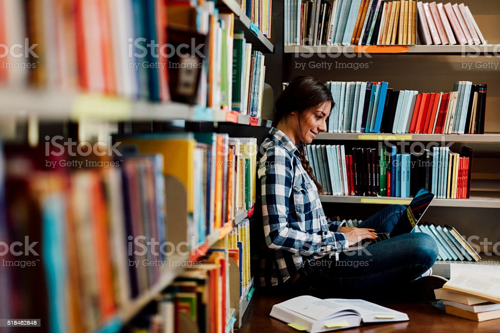 Student in the library using laptop. stock photo