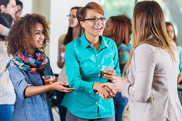 student introducing parent to teacher during meet and greet party - family meeting stock photos and pictures