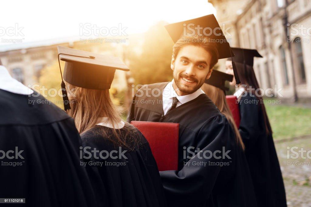 Ein Student posiert für eine Kamera, stehen im Innenhof der Universität mit Freunden. – Foto