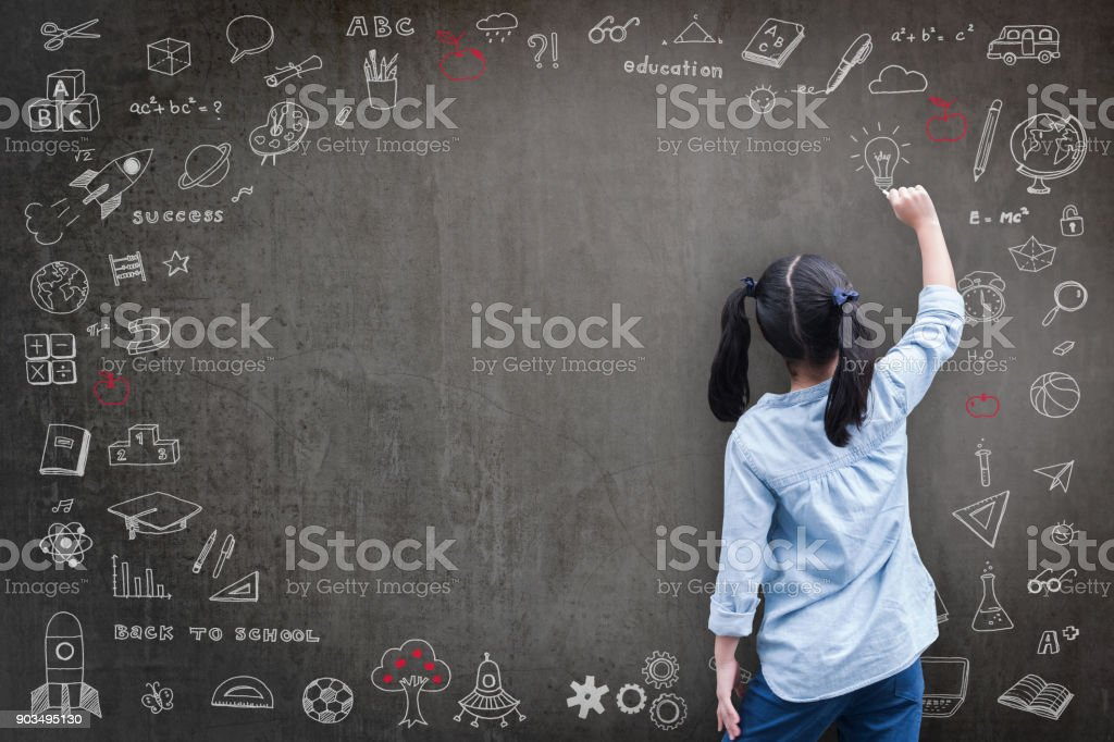 Student kid back view drawing doodle on school chalkboard stock photo