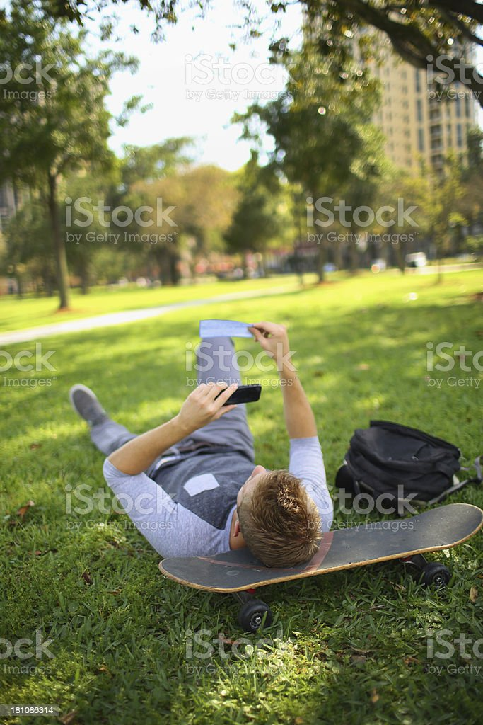 Student laying on grass depositing his check with his phone stock photo