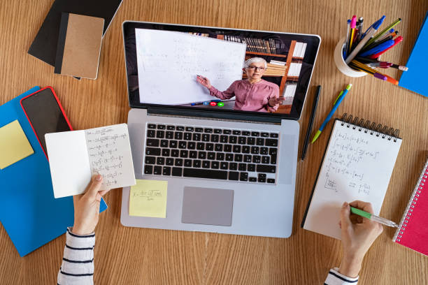 Student learning at home with online lesson High angle view of video conference with teacher on laptop at home. College student learning maths while watching online webinar, listening audio course. Top view of girl in video call with personal tutor on computer, distance and e-learning education concept. desolation stock pictures, royalty-free photos & images