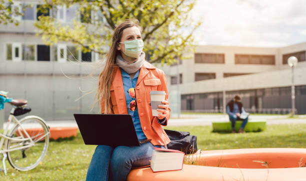 Student learning on university campus during covid-19 lockdown stock photo
