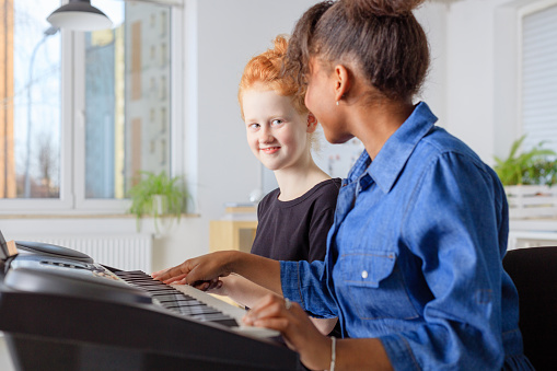 Student Learning Piano From Teacher In Music Class Stock Photo - Download Image Now