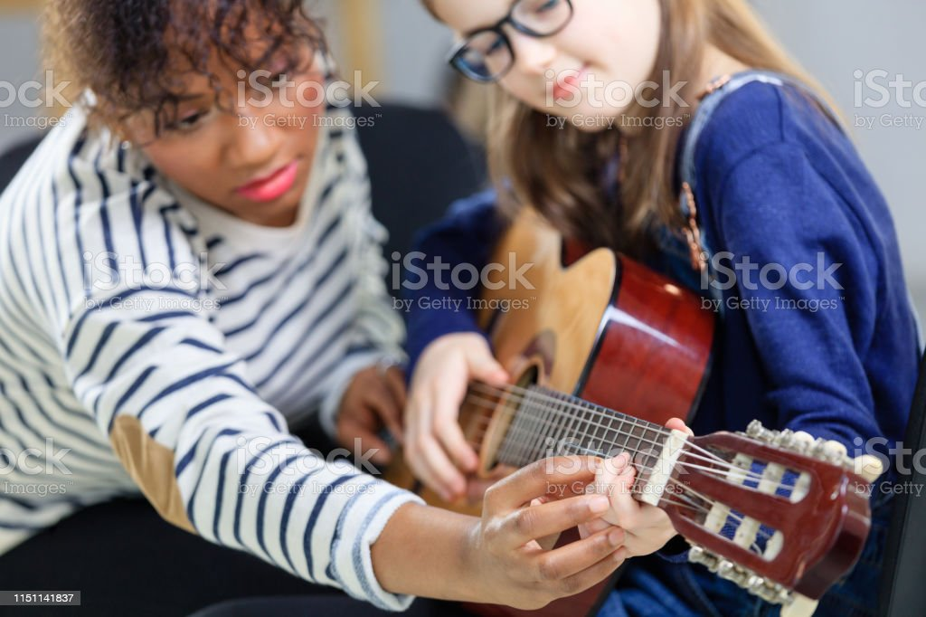 Student learning string instrument from guitarist Instructor assisting girl in plucking guitar strings. Pre-adolescent student is learning string instrument from female teacher in music class. They are at education building. 10-11 Years Stock Photo
