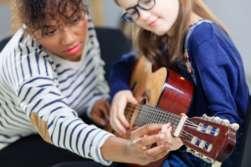Student Learning String Instrument From Guitarist Stock Photo - Download Image Now