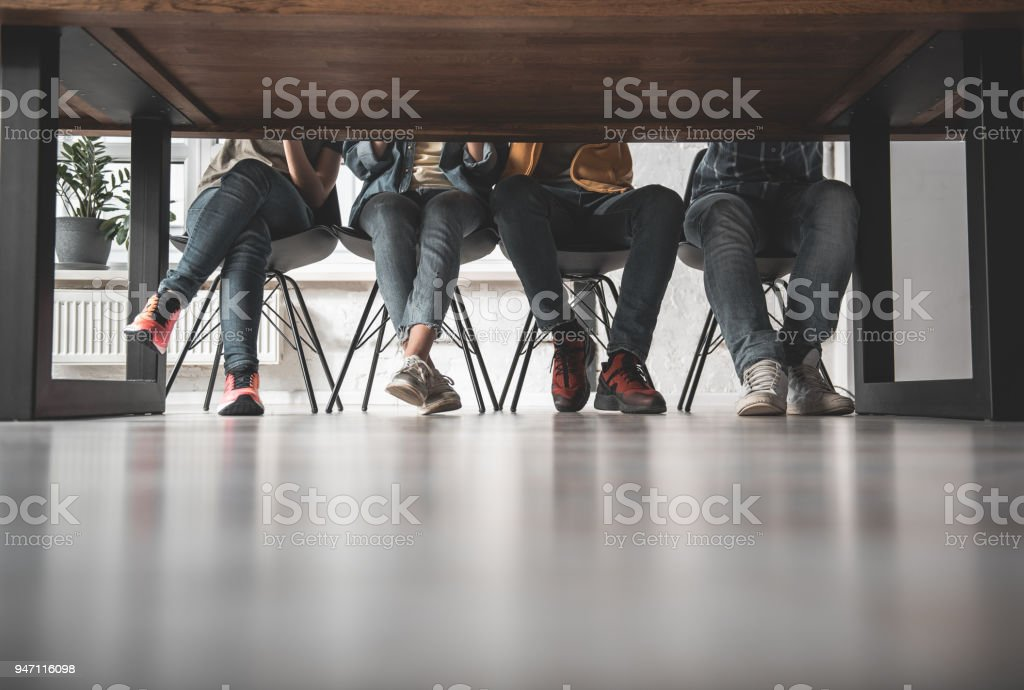 Student legs in jeans and snickers stock photo