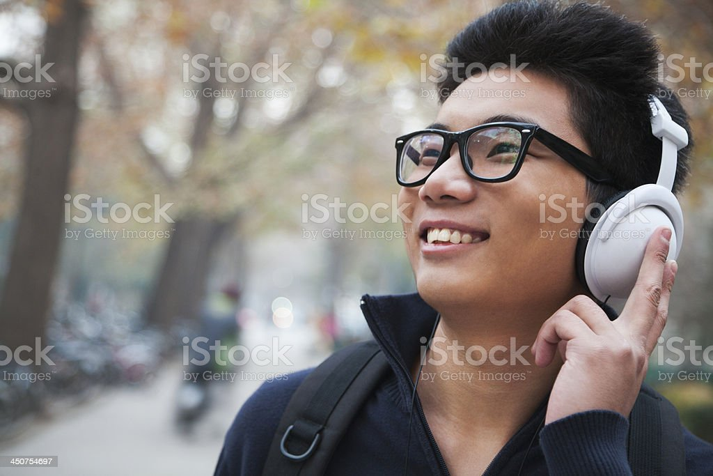 Student listening to music on college campus stock photo