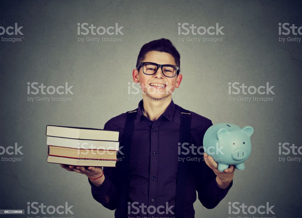 Student loan concept. Happy man with stack pile of books and piggy bank full of debt stock photo