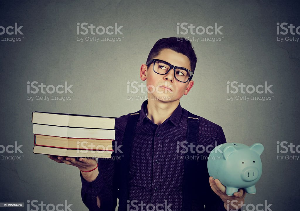 Student loan debt. Man with books piggy bank stock photo