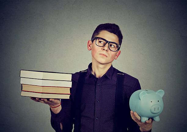 Student loan debt. Man with books piggy bank stock photo