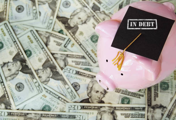 Student Loan debt piggy with In Debt graduation cap on money borrowing stock pictures, royalty-free photos & images
