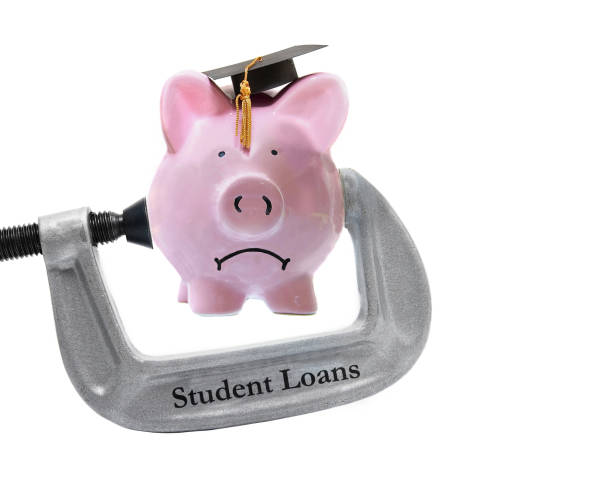 student loan piggy bank in a vice stock photo
