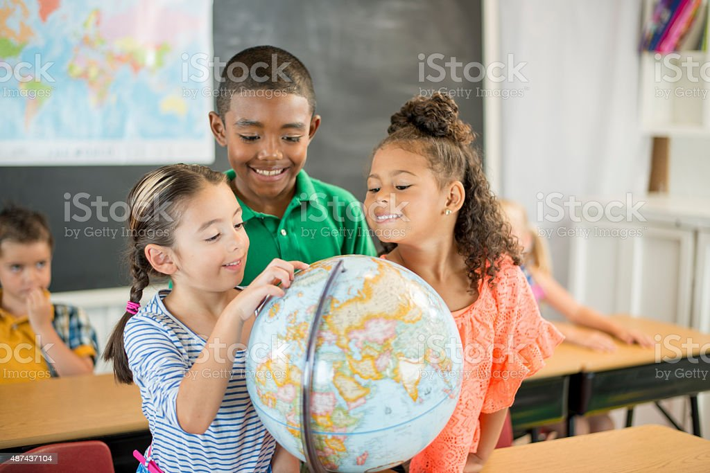 Student Looking at a Globe A multi-ethnic group of elementary age children are looking at a globe in their classroom. 2015 Stock Photo