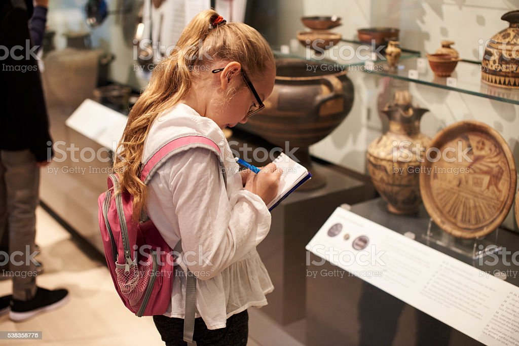 Student Looking At Artifacts In Case On Trip To Museum stock photo