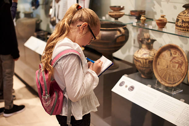 student looking at artifacts in case on trip to museum - museum stockfoto's en -beelden