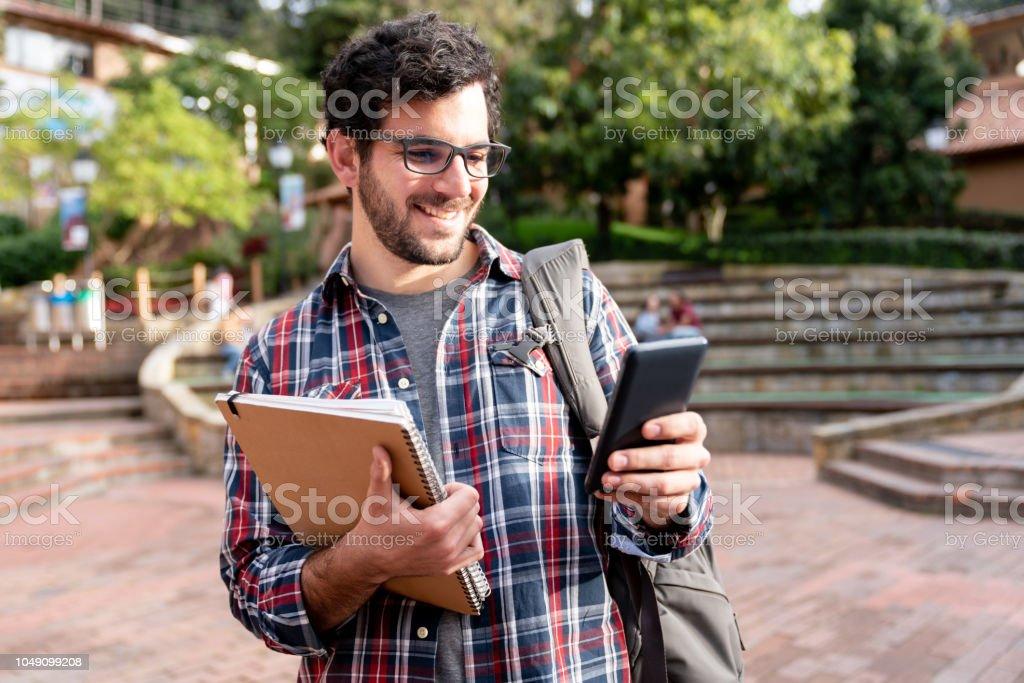 Étudiant à la recherche sur les médias sociaux sur son téléphone cellulaire à l'Université - Photo