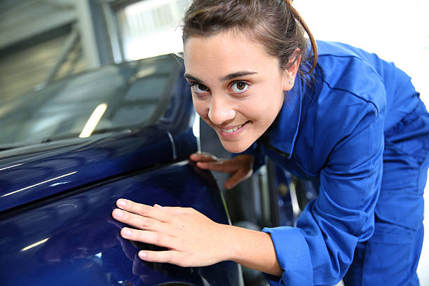 Student looking at the bodywork of car in garage stock photo