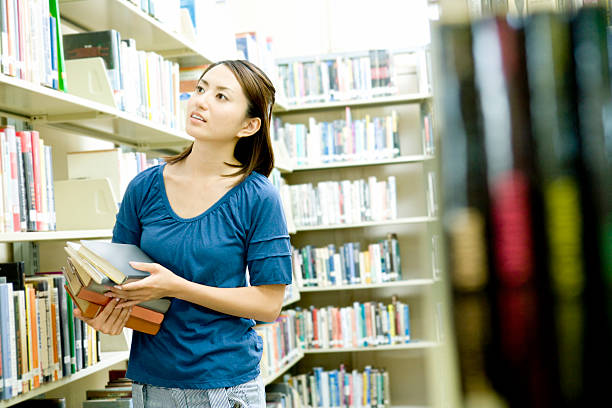 Student looking for book in library stock photo