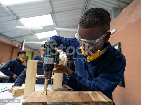 Design student making a piece of furniture in class and drilling a piece of wood - education concepts