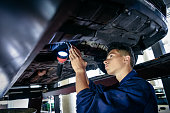 istock Student mechanic examining car with torch 827810816
