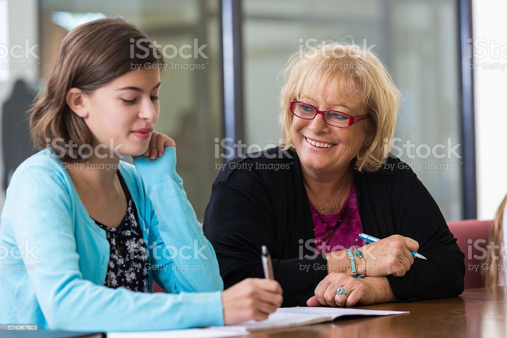 Student meeting with school counselor in office stock photo