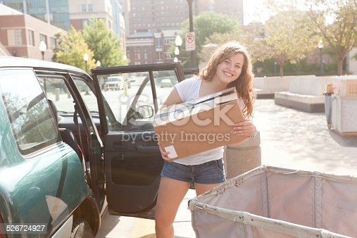 istock Student Moving Box from Car to Dormitory on College Campus 526724927