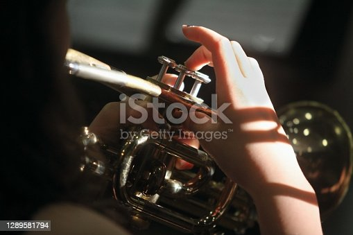Close-up of the hands of a student musician as she plays a trumpet.