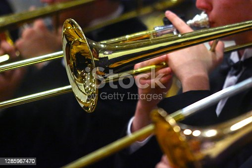 Student musicians play trombones in a close-up image.
