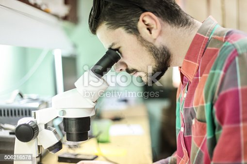 Student or worker looking through microscope. About 25 years old Caucasian male with beard in casual clothing.