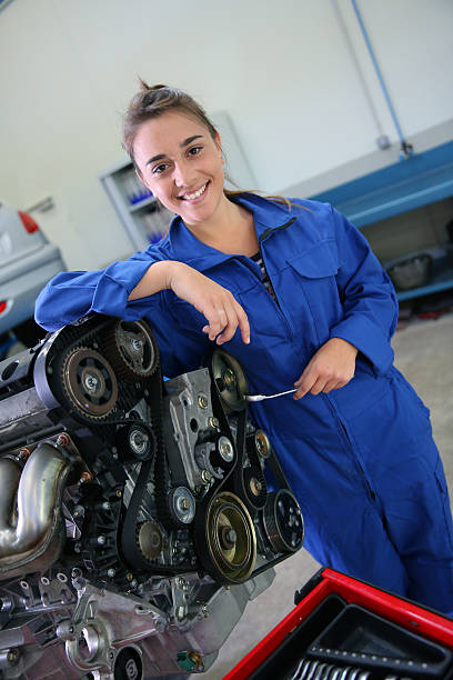 Student of mechanics leaning on motor in a garage stock photo