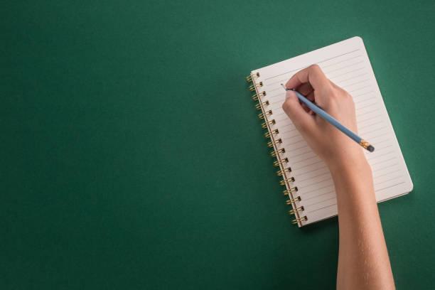 Student der Mädchen Hand vom Bleistift mit Notizbuch auf einem grünen Hintergrund. – Foto