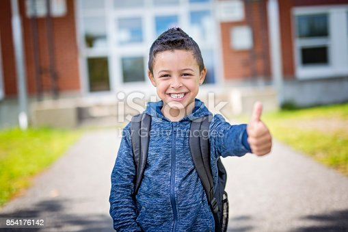 istock student outside school standing smiling 854176142