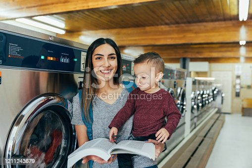A mother and parent sits with her toddler son at a laundromat while studying for a university class. She is a hard working college student trying to earn her degree in education to improve her situation. She helps to occupy her son with reading a book.