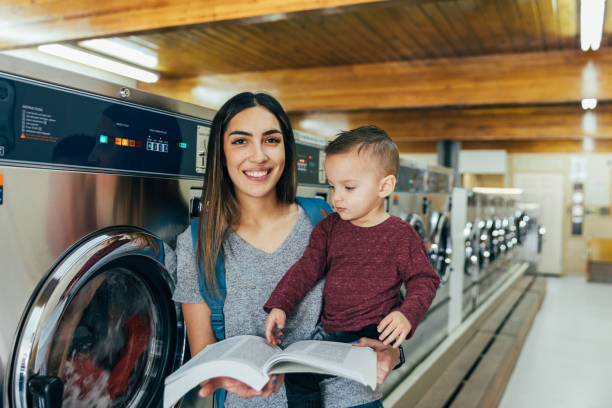 Student Parent Reading at Laundromat with Son stock photo