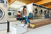 A mother and parent sits with her toddler son at a laundromat while studying for a university class. She is a hard working college student trying to earn her degree in education to improve her situation.