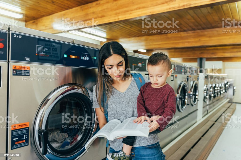 Student Parent Studying at Laundromat A mother and parent sits with her toddler son at a laundromat while studying for a university class. She is a hard working college student trying to earn her degree in education to improve her situation. 18-23 Months Stock Photo