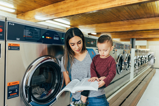 Student Parent Studying At Laundromat Stock Photo - Download Image Now