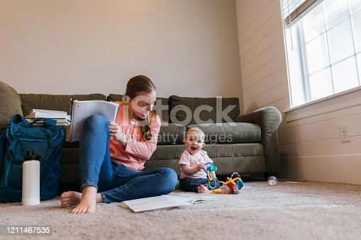 A mother and parent sits with her baby daughter on the family room floor studying for a university class. She is a hard working college student trying to earn her degree in education to improve her situation.