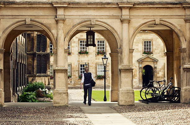student passing through a college campus in cambridge universitiy, uk - cambridge university stock photos and pictures