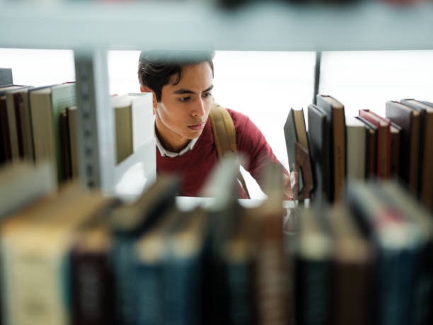 Student picking a book from a library stock photo