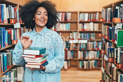 istock Student picking books in the library 1133871949