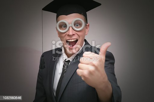Graduate student in the cap is showing a thumbs up isolated on gray background. Education concept.