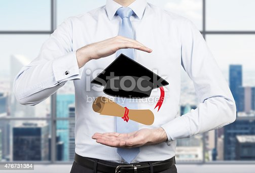 istock student placing his hands around the graduation attributes. 476731384