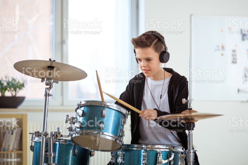 Student playing drums while listening music at class Little drummer playing drums while listening music. Male student is practicing percussion instrument in class. He is wearing casuals at education building. 12-13 Years Stock Photo