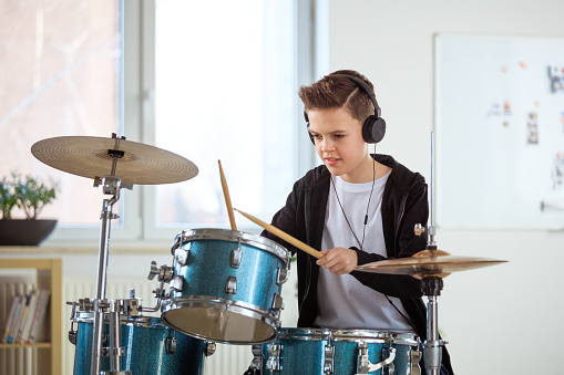 Student Playing Drums While Listening Music At Class Stock Photo - Download Image Now