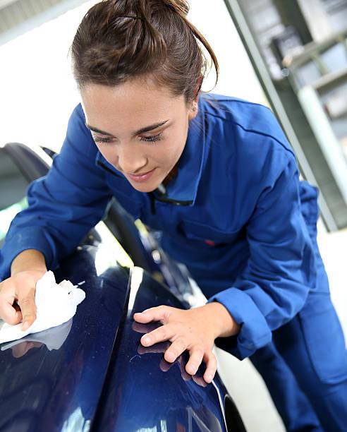 Student polishing the bodywork of car in garage stock photo